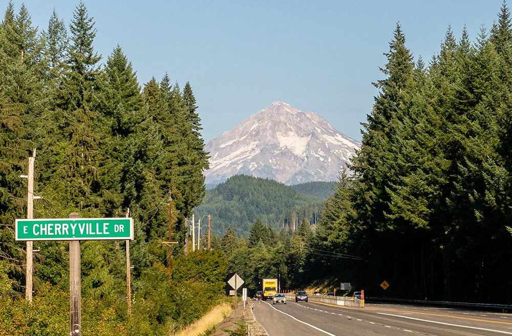 mount hood in the distance as traffic travels down a road near portland in oregon